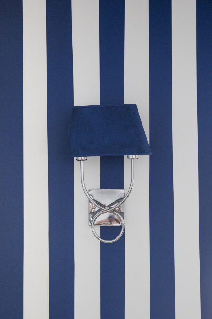 blue and white painted wall stripes with wall sconce light