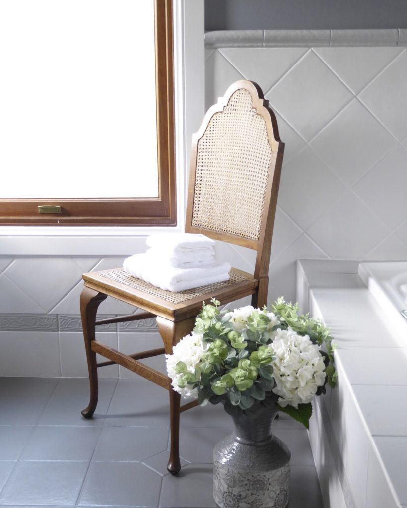 kids bathroom makeover completed antique chair and vase with florals